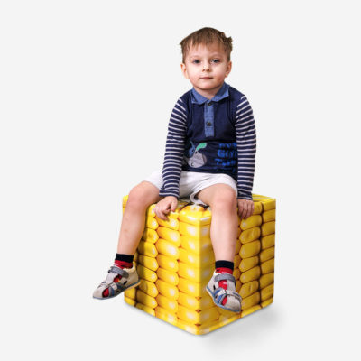 Boy is sitting on corn cube