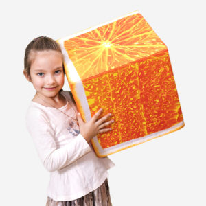 Girl is standing with orange cube