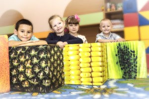 children on corn, pineapple and kiwi cube seats