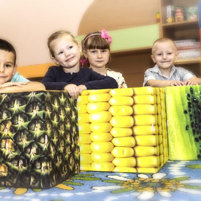 children on corn, pineapple and kiwi cube seats