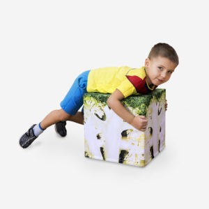 boy is lying on broccoli cube on white background